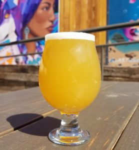 hazy yellow ipa beer on a table