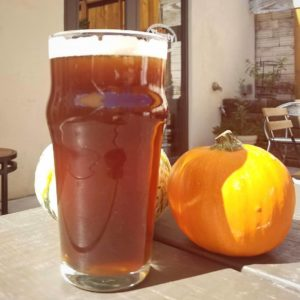 a glass of beer sitting in front of two pumpkins